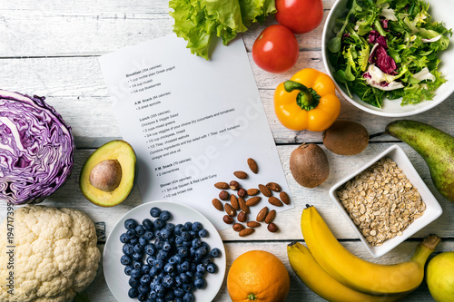 Wall mural balanced diet plan with fresh vegetables and fruits on the table