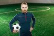 Young confident football trainer in sportswear looking at camera while standing on pitch