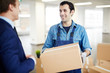 Delivery man with box talking to owner of new office area while carrying package