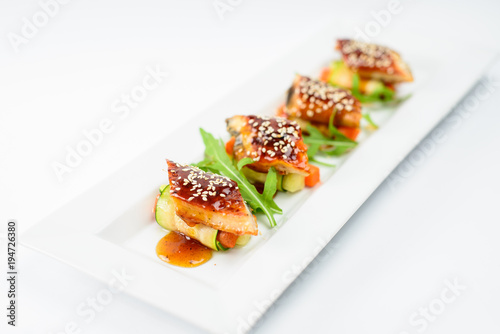 Fotobehang Sushi bar Sushi rolls with sesame seeds on a white plate, high cuisine