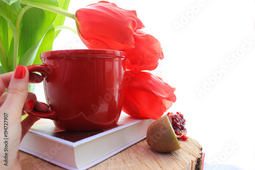 Fototapeta Morning concept. Healthy lifestyle. Red flat lay: fresh fruits kiwi, pomegranate. Red tulips and cup on the book. Close up