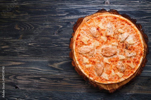 Papiers peints Pizzeria Appetizing freshly baked pizza with chicken and pineapple served on chopped wood, flat lay with copy space. Italian restaurant menu concept