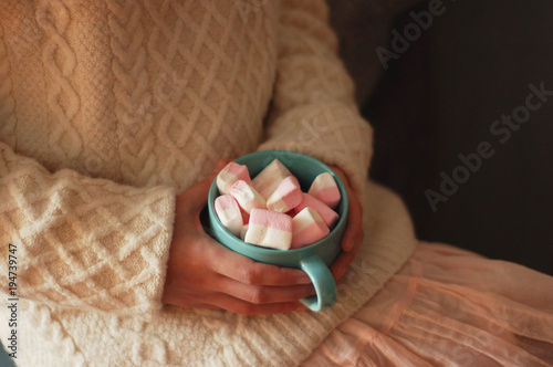 Fotobehang Chocolade cozy dreams: the lovely girl holds a blue cup with pink marshmallow in her hands