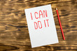 Sheet of white paper with text with red pencil on wooden background. Concept of motivation