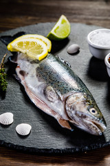 Fresh raw trout served on black stone on wooden table