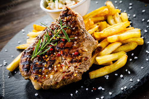 Foto op Canvas Steakhouse Grilled steak with french fries and vegetables served on black stone on wooden table