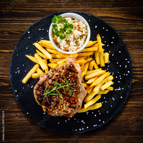Aluminium Steakhouse Grilled steak with french fries and vegetables served on black stone on wooden table