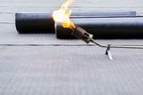 Heating and melting bitumen - roofing felt Flat roof installation - 194749923