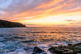 sunset over rocky sea - 194756347