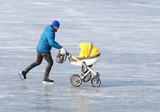 Young father with baby stroller. Skating on frozen lake. Winter sports and leisure activities theme. - 194762721