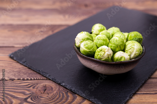 Fotobehang Brussel Fresh Brussels sprouts in a bowl on a black slate on a wooden table. Place for text.