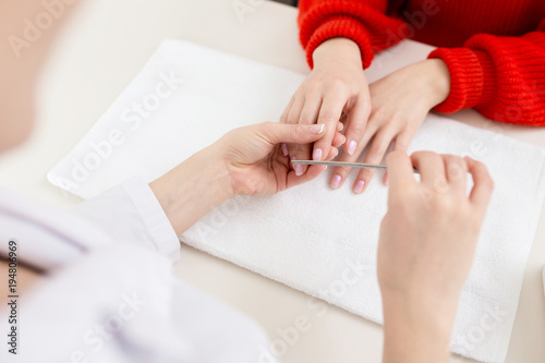 Poster Manicure Close-up shot of unrecognizable client wearing knitted sweater receiving procedure in modern nail salon
