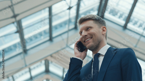 Foto Murales Young businessman talking on the phone