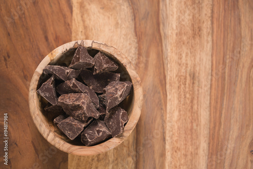 top view dark chocolate chunks in wood bowl on table