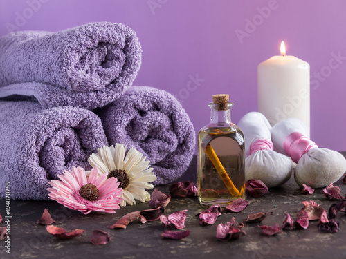 Spa treatment and massage products with towels and oil on stone with violet color background