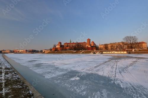 Fotobehang Krakau Piękny zimowy pejzaż zamku na Wawelu w Krakowie z zamarzniętą rzeką Wisłą na pierwszym planie, światło zachodzącego słońca, na lodzie na rzece ślady sanek i butów
