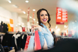 Smiling girl with shopping bags in shop - 194822709