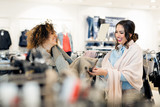 Two young attractive girlfriends go shopping - 194823587