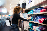 Two young girls look at clothing in store - 194823596