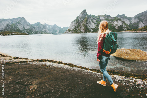 Backpacker woman walking alone in Norway lifestyle travel concept adventure outdoor summer vacations