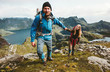 Happy Couple hiking in Norway mountains love and travel holding hands man and woman together Lifestyle concept vacations outdoor
