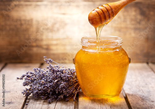 pouring honey into jar of lavender honey