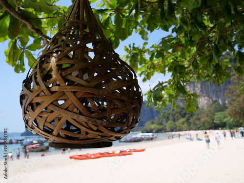 Fotobehang Bamboe Wicker lantern at the tree over blurred silhouettes of people on the beach during sunny summer day