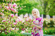 Young woman under blooming magnolia tree on a spring day
