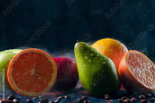 Papiers peints Café en grains Wet and fresh fruit lie on a black background and in smoke