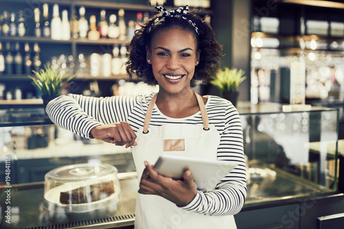 Fototapeta Smiling African entrepreneur standing in her cafe with a tablet