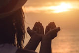 Girl's hands / palms in the air with ocean sunset.