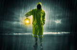 Man walking in storm with lantern - 194858361