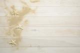 Conchas, estrellas de mar y caracolas marinas sobre fondo de madera blanca con arena - 194858904