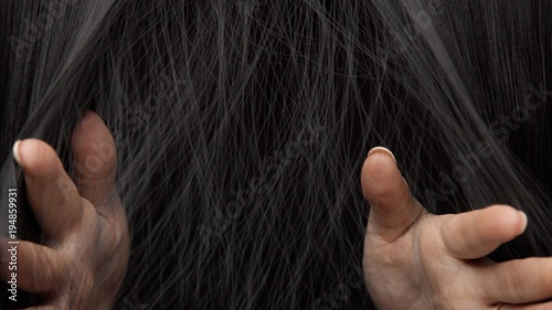 Hair texture background, no person. Black shiny hair Hands touching it
