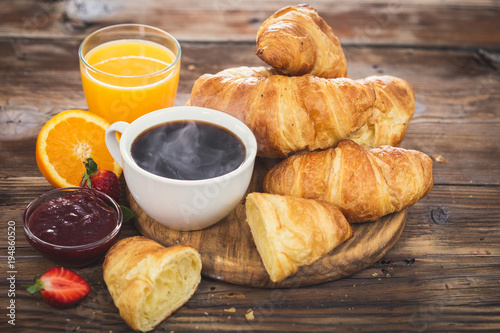 Wall mural Fresh homemade croissants with black coffe and orange juice