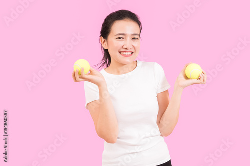 Fotobehang Tennis Cute asian woman with tennis balls, sport and exercise concept, portrait, white shirt, pink background