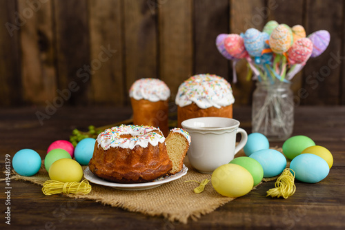 Wall mural Easter cake and colorful eggs on a wooden table. It can be used as a background