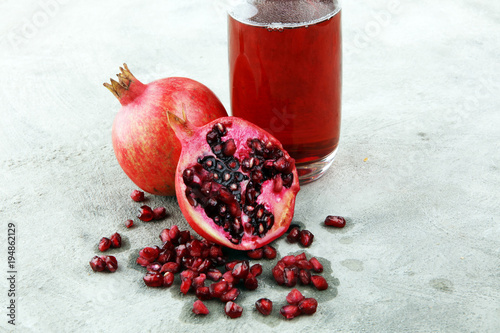 Foto op Canvas Sap Glass of pomegranate juice and pomegranate fruit on old background
