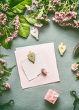 Greeting preparation with blank paper card mock up with heart and gift box on florist desktop with green leaves and flowers , top view, flat lay - 194867544