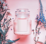 Natural cosmetics jar with pastel pink cream or peeling , herbal leaves and wild flowers, blank label for branding mock-up on pastel background, top view - 194868566