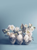 Easter concept with eggs and decorative white blossom bunch on pastel blue background, front view, copy space - 194868717