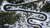 Winding road from high mountain pass, in winter time. Aerial view by drone . Romania