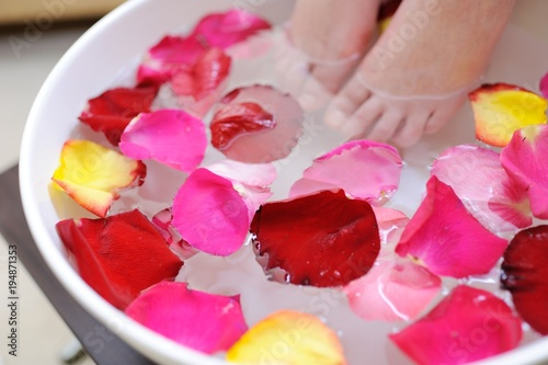 Tuinposter Pedicure Female feet in rose petals pedicure. Spa procedure