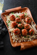 Traditional roasted meatballs with rice and tomato sauce on a wooden plate. - 194872389
