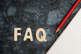 FAQ word with red pencil and book paper. Question and answer concept