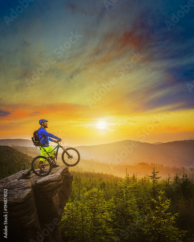 Fototapeta Mountain biker riding at sunset on bike in summer mountains forest landscape. Man cycling MTB flow trail track. Outdoor sport activity.