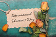 International Women's Day card, Dried orange roses on old wooden background,