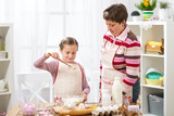 Mother and daughter cook at home. make the dough for buns - 194889306