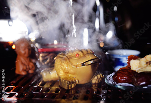 Foto op Canvas Zen Clay three-toed tea toad with a coin in his mouth on the background of a tea table. Tea ceremony
