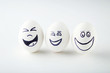 Eggs with funny faces on white background